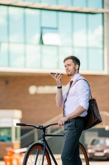 Jovem empresário elegante gravando mensagem de voz no smartphone enquanto está sentado em uma bicicleta contra o exterior de um edifício contemporâneo