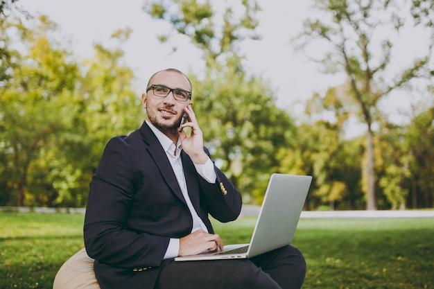 Jovem empresário em camisa branca, terno clássico, óculos. homem sentar no pufe macio, trabalhar no computador laptop pc, falar no celular no parque da cidade, no gramado verde ao ar livre. escritório móvel, conceito de negócio.