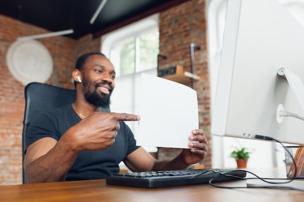 Jovem, empresário em casa, olhando para a tela preta do computador em branco, monitor