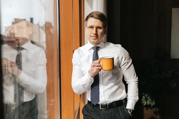 Jovem empresário em pé com uma xícara de café na janela de seu escritório