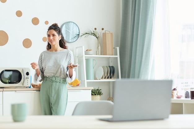 Jovem empresário em pé na cozinha discutindo algo com os colegas usando o aplicativo de reunião on-line no smartphone