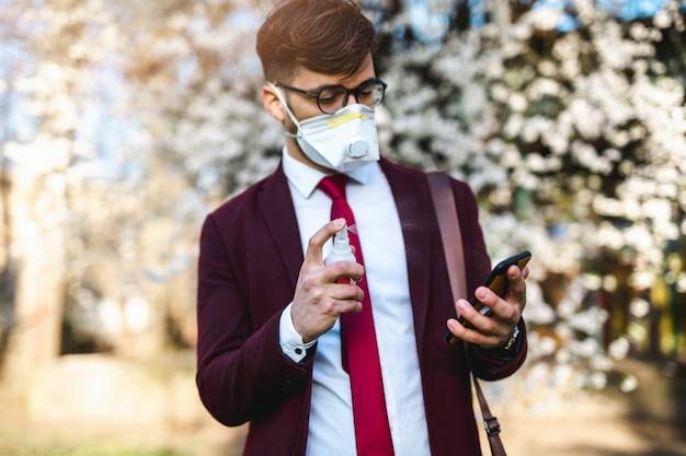 Jovem empresário em pé no parque, usando máscara protetora e desinfetando o telefone inteligente com álcool.