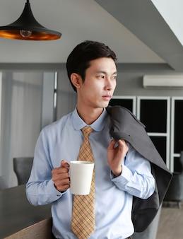 Jovem empresário em pé perto da mesa no local de trabalho no escritório com café e beber