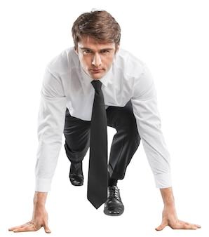 Jovem empresário em pose inicial para correr em segundo plano