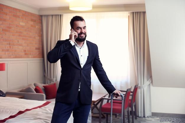 Jovem empresário em quarto de hotel com smartphone