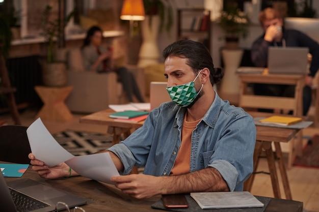 Jovem empresário em roupas casuais, trabalhando com máscara protetora em sua mesa com documentos no escritório
