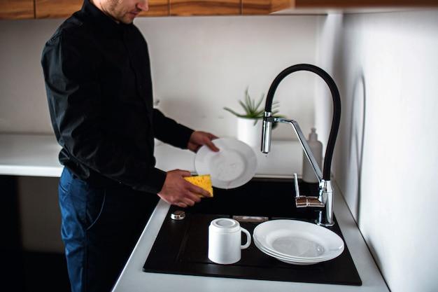 Jovem empresário em roupas pretas, lavar a louça na cozinha