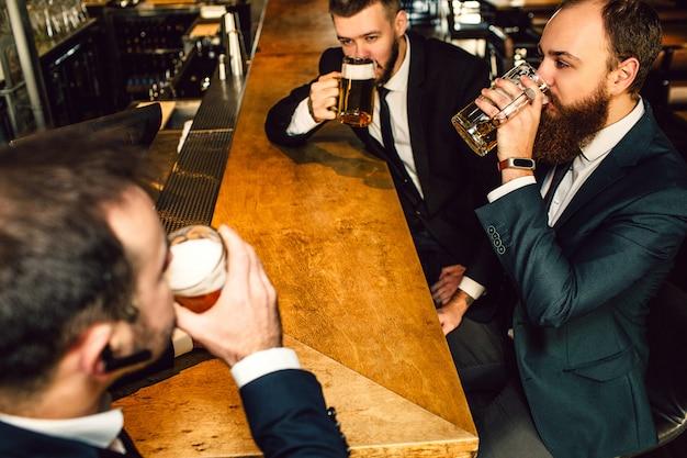 Jovem empresário em terno bebe urso em bar. eles se sentam um na frente do outro.
