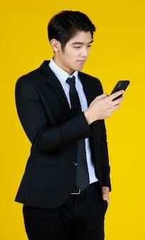 Jovem empresário em terno preto formal. olhar de pé para o telefone móvel parece mensagem de texto. o fundo amarelo dá um toque moderno. o espaço pode ser preenchido com texto.