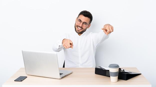 Jovem empresário em um local de trabalho aponta o dedo para você enquanto sorrindo