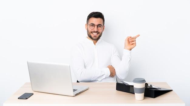 Jovem empresário em um local de trabalho, apontando o dedo para o lado