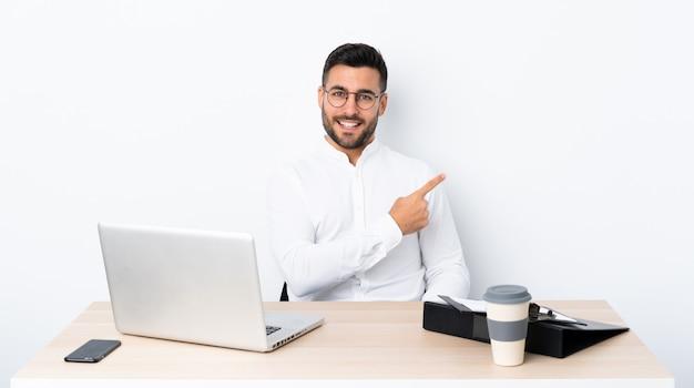 Jovem empresário em um local de trabalho, apontando para o lado para apresentar um produto