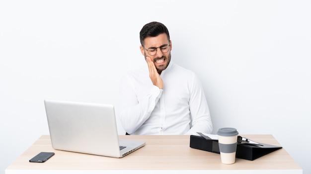 Jovem empresário em um local de trabalho com dor de dente