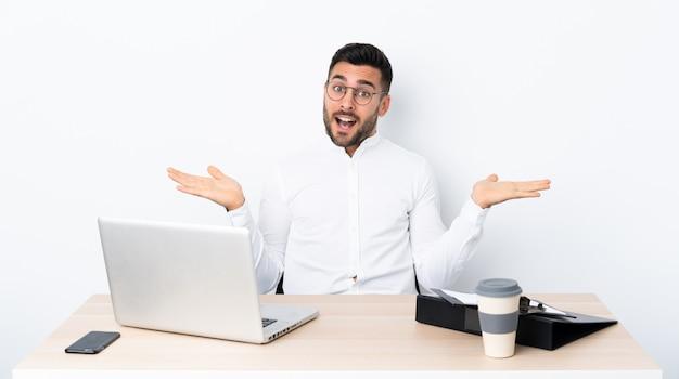 Jovem empresário em um local de trabalho com expressão facial chocado