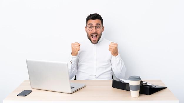 Jovem empresário em um local de trabalho comemorando uma vitória na posição de vencedor