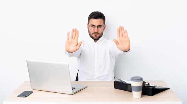 Jovem empresário em um local de trabalho, fazendo o gesto de parada e decepcionado