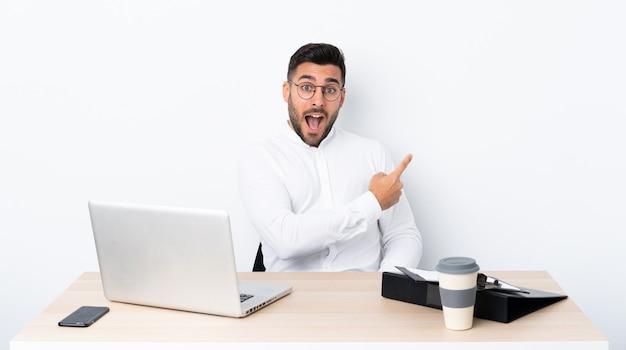 Jovem empresário em um local de trabalho surpreso e apontando o lado