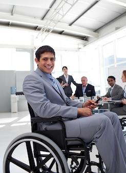 Jovem empresário em uma cadeira de rodas em uma reunião