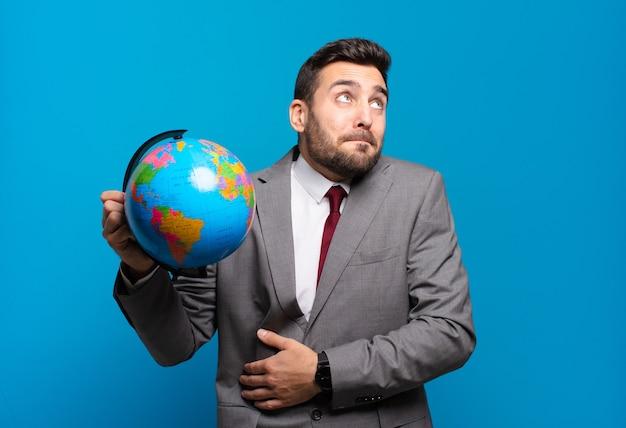 Jovem empresário encolhendo os ombros, sentindo-se confuso e inseguro, duvidando com os braços cruzados e olhar perplexo segurando um mapa do globo terrestre