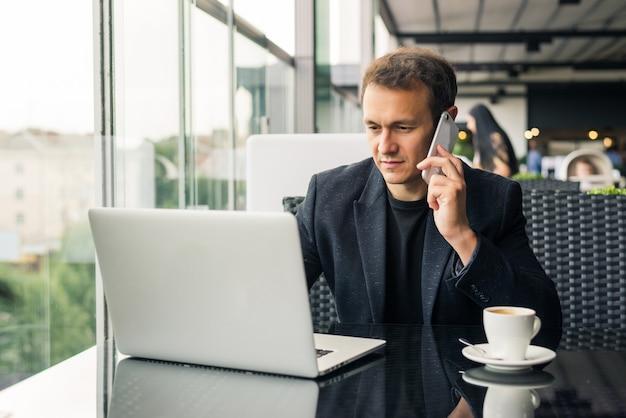 Jovem empresário enviando mensagens de texto ao telefone com um laptop na mesa do café