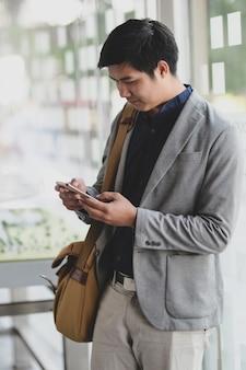 Jovem empresário, escondendo o smartphone enquanto sai do escritório