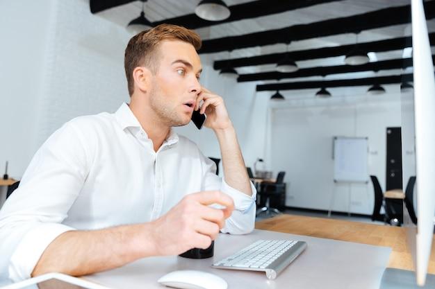 Jovem empresário espantado a beber café e a falar ao telemóvel no escritório