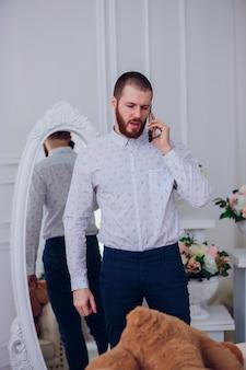 Jovem empresário está com raiva. falando por telefone. macho descontente falando ao telefone no fundo do espelho