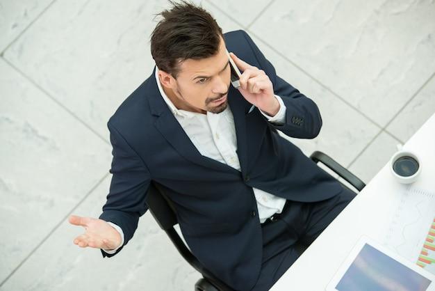 Jovem empresário está falando por telefone no trabalho.