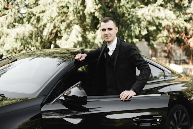 Jovem empresário está sentado em um carro caro e olhando para a câmera. o noivo está dirigindo. homem de negocios. cara de sucesso. homem rico.