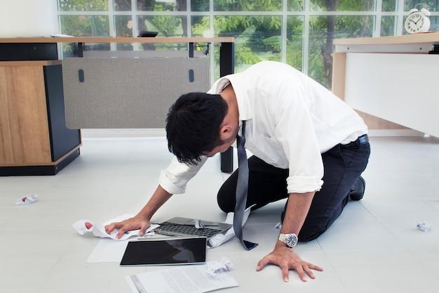 Jovem empresário estressado e sobrecarregado gritando no escritório.