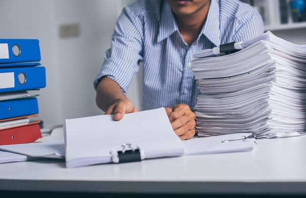 Jovem empresário exausto asiático com mesa bagunçada e pilha de papéis, trabalhando ocupado, excesso de trabalho.