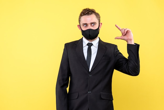 Jovem empresário expressando forma de solução com máscara facial em amarelo