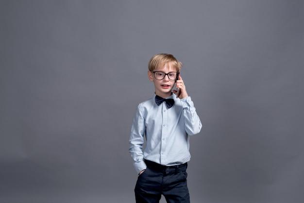 Jovem empresário falando ao telefone. garotinho posando em um cinza