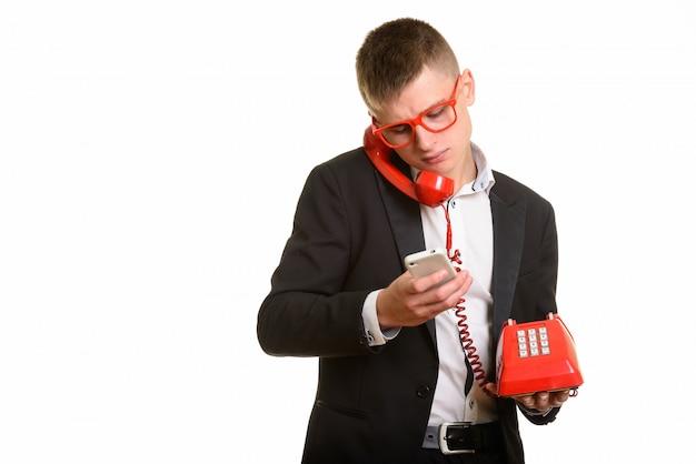 Jovem empresário falando no telefone antigo enquanto