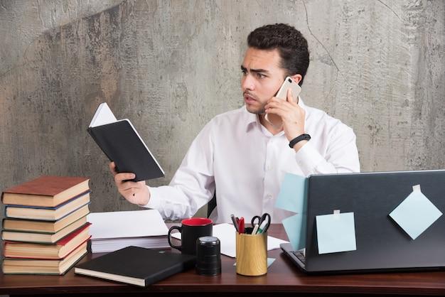 Jovem empresário falando sobre negócios na mesa do escritório.