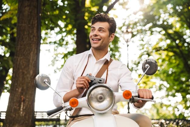Jovem empresário feliz andando de moto ao ar livre, tirando fotos com uma câmera fotográfica