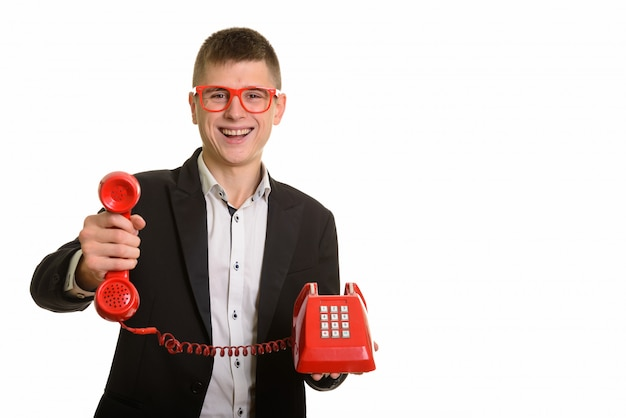 Jovem empresário feliz sorrindo e dando telefone antigo