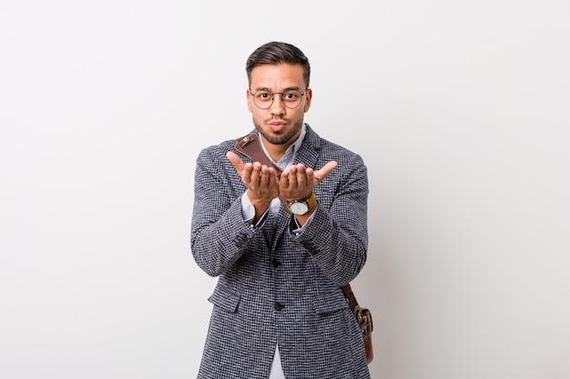 Jovem empresário filipino contra uma parede branca, dobrando os lábios e segurando as palmas das mãos para enviar beijo no ar.
