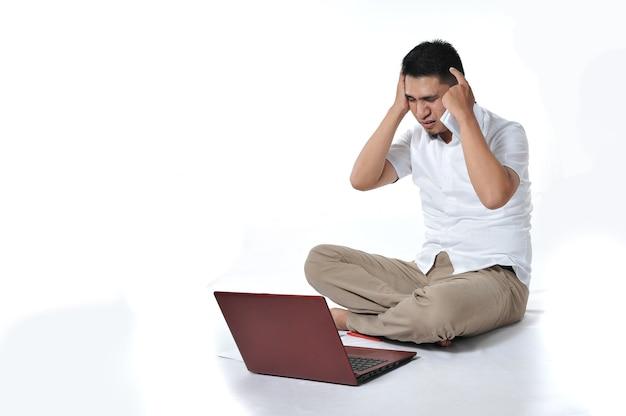 Jovem empresário / freelancer asiático ou homem de negócios tonto ou zangado, isolado no branco