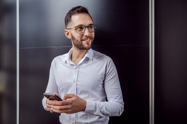 Jovem empresário geeky sorridente em frente a parede, digitando a mensagem no telefone inteligente e desviar o olhar.
