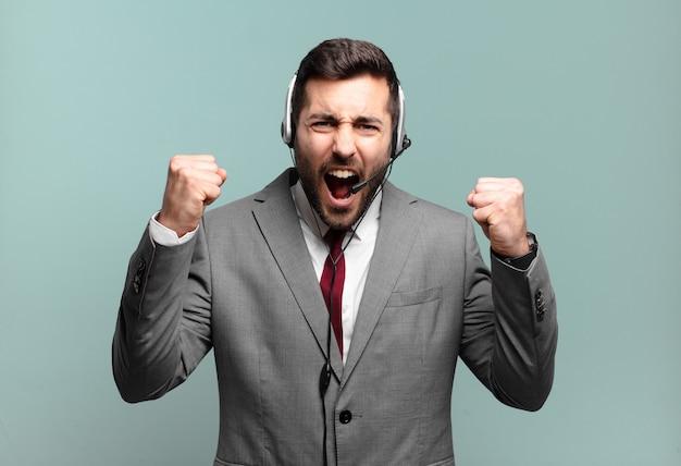 Jovem empresário gritando agressivamente com uma expressão de raiva ou com os punhos cerrados celebrando o conceito de telemarketing de sucesso