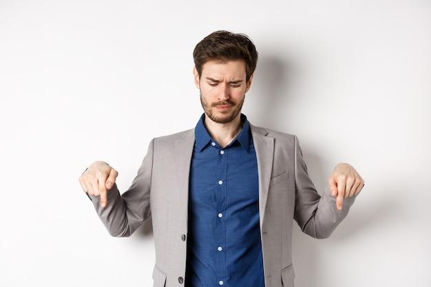 Jovem empresário impressionado, franzindo a testa desapontado, apontando e olhando para a má promoção, descontente em pé no fundo branco.