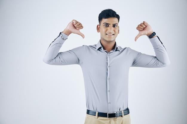Jovem empresário indiano ambicioso e confiante apontando para si mesmo com os dois polegares