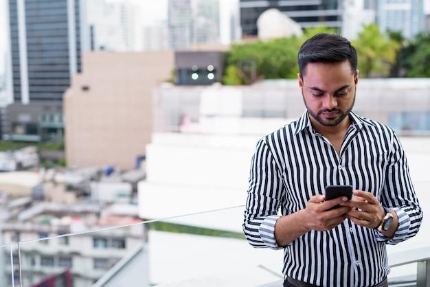 Jovem empresário indiano barbudo contra a vista da cidade