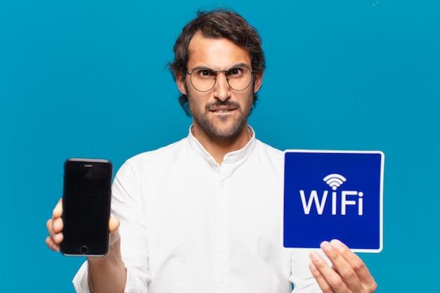 Jovem empresário indiano bonito mostrando sua tela vazia do celular.