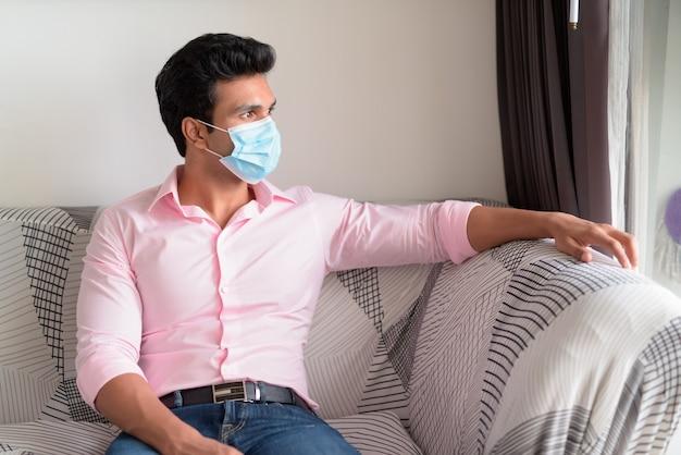 Jovem empresário indiano com máscara pensando e ficando em casa em quarentena