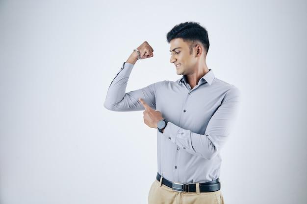 Jovem empresário indiano empolgado apontando para os músculos rígidos do bíceps, isolados no branco