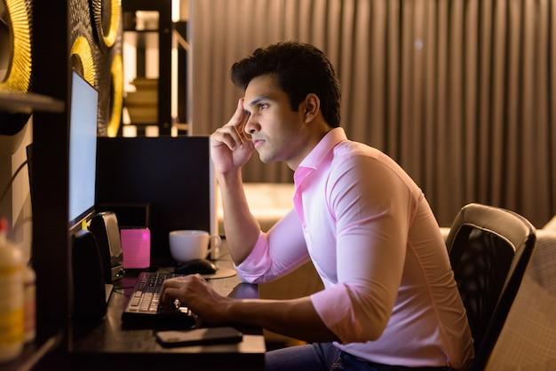 Jovem empresário indiano estressado pensando enquanto trabalhava horas extras em casa tarde da noite