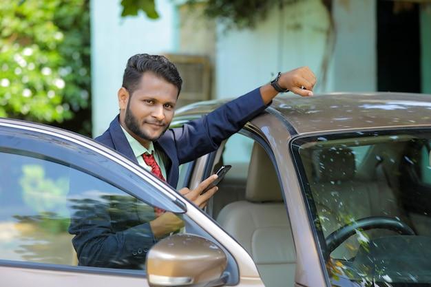 Jovem empresário indiano parado do lado de fora do carro e usando telefone celular