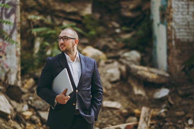 Jovem empresário inteligente de sucesso em camisa branca, terno clássico, óculos. homem de pé com o telefone do computador laptop pc perto de ruínas, detritos, edifício de pedra ao ar livre. escritório móvel, negócios, conceito de trabalho.